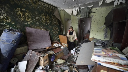 A woman surveys damage in her flat on December 9, 2014 after it was destroyed by shelling the night before in the Kuibishevskiy district of the eastern Ukrainian city of Donetsk, which is controlled by pro-Russian rebels. Planned peace talks between Ukraine and pro-Russian rebels were postponed on December 9, but a ceasefire appeared to be largely holding along the frontline in the ex-Soviet republic's war-shattered east.  AFP PHOTO / ERIC FEFERBERG